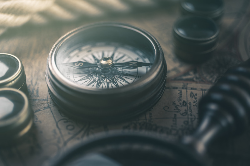 A vintage compass lying on a map.