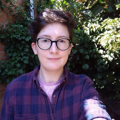 Jake, a white trans masculine person with short brown hair and round glasses.